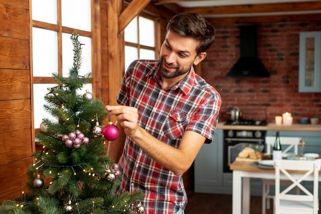 Medium Shot Man Decorating The Christmas Tree Photo