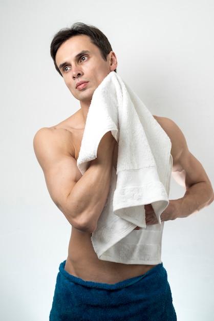 Medium shot man drying body after bath Free Photo