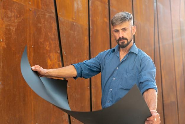 Medium shot of man holding blueprint Free Photo