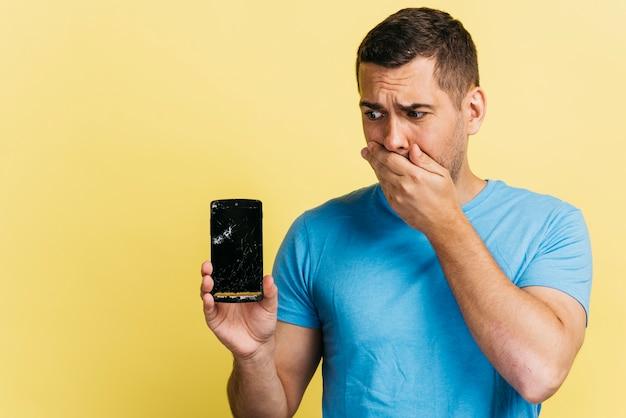 Medium shot man holding a broken phone Free Photo