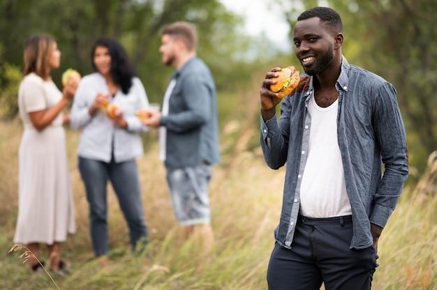 ハンバーガーを持っているミディアムショットの男 無料写真