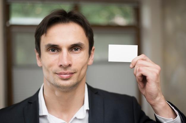 Medium shot of man holding business card Free Photo