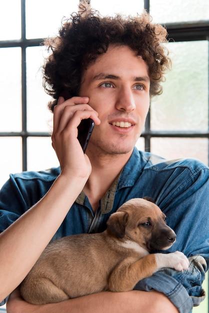 かわいい犬を抱きかかえたミディアムショットの男 無料写真