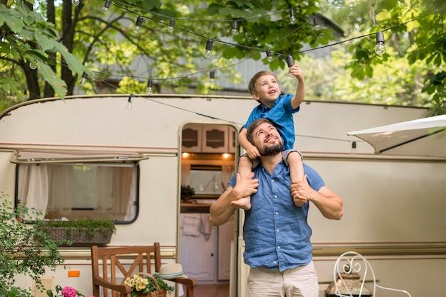 Мужчина среднего роста держит сына на плечах рядом с караваном Бесплатные Фотографии