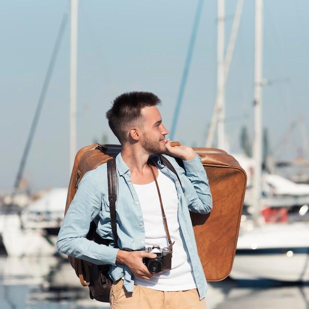 Средний выстрел мужчина держит багаж Premium Фотографии