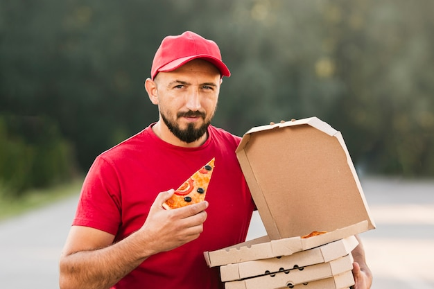 Medium shot man holding pizza slice Free Photo