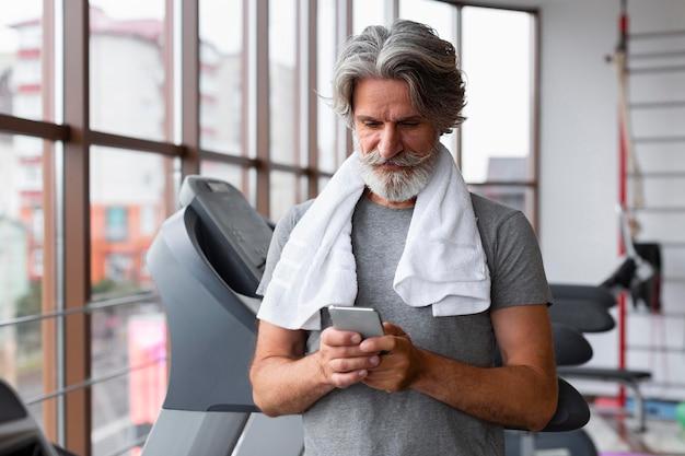 スマートフォンを保持しているミディアムショットの男 無料写真