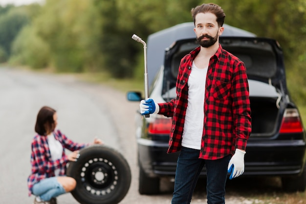 Medium shot of man holding tyre wrench Free Photo
