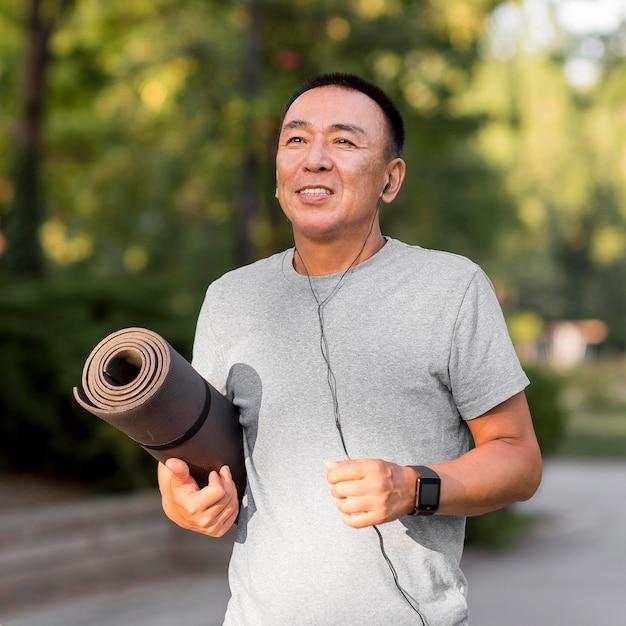 Средний снимок человека, держащего коврик для йоги Бесплатные Фотографии