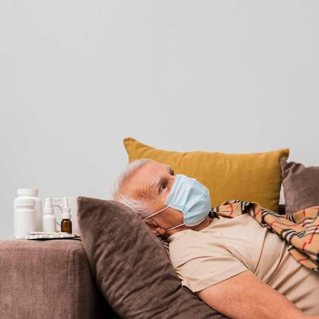 Medium shot man laying on couch with mask Free Photo