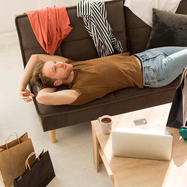 Colpo medio uomo posa sul divano Foto Gratuite