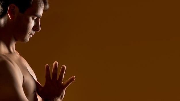 Medium shot man meditating with copy space Free Photo