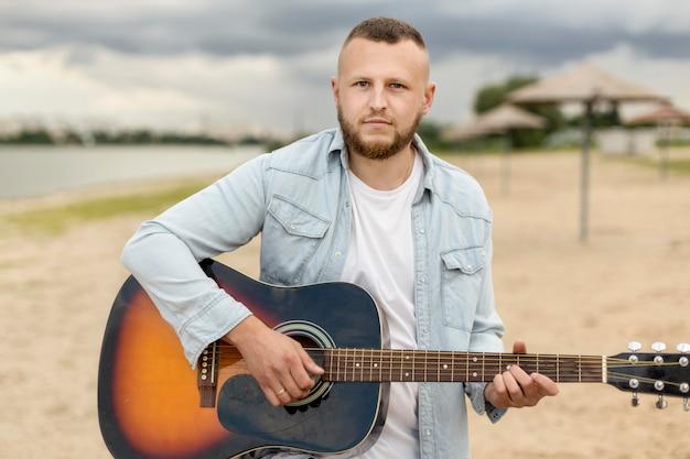 Средний выстрел мужчина играет на гитаре на пляже Бесплатные Фотографии