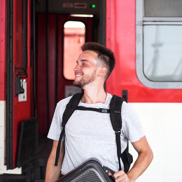 Мужчина среднего кадра позирует возле поезда Бесплатные Фотографии