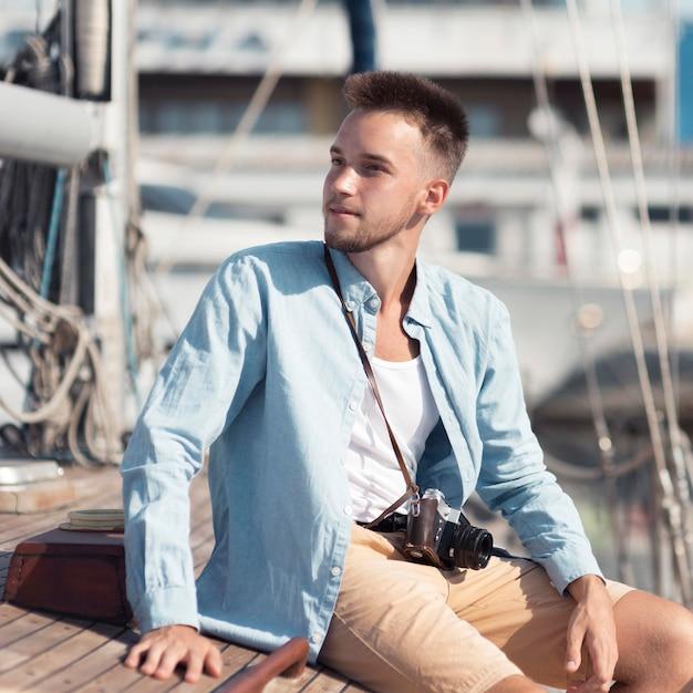 Средний выстрел человек сидит на лодке Premium Фотографии