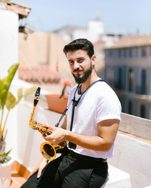 Medium shot man sitting with saxophone Free Photo