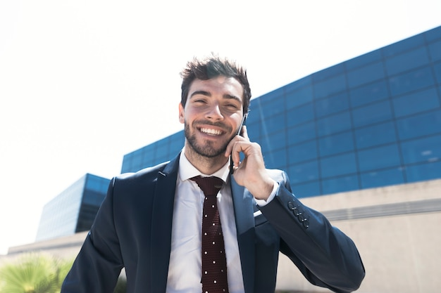 Medium shot man in suit talking on the phone Free Photo
