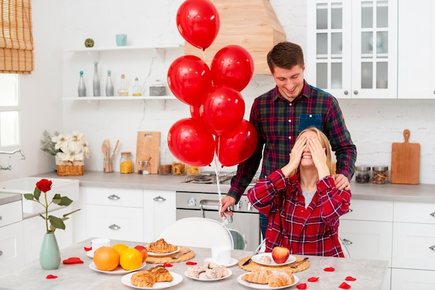 Medium shot man surprising woman with balloons Free Photo