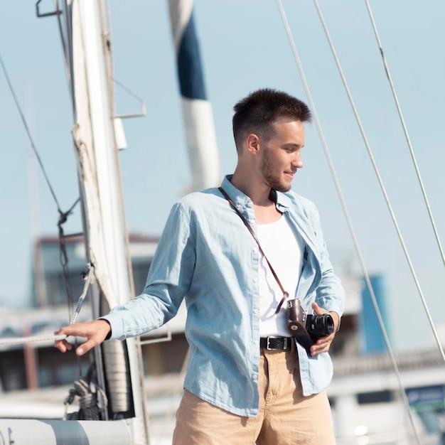 Средний снимок человека с камерой на лодке Premium Фотографии