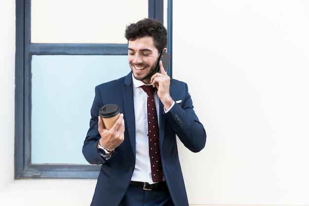 Medium shot man with coffee talking on the phone Free Photo