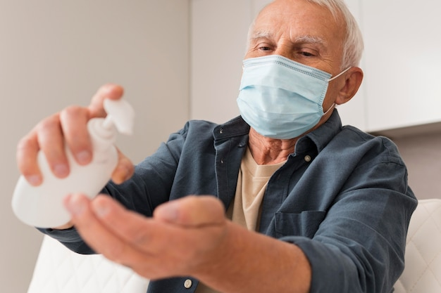 Medium shot man with mask and disinfectant Free Photo