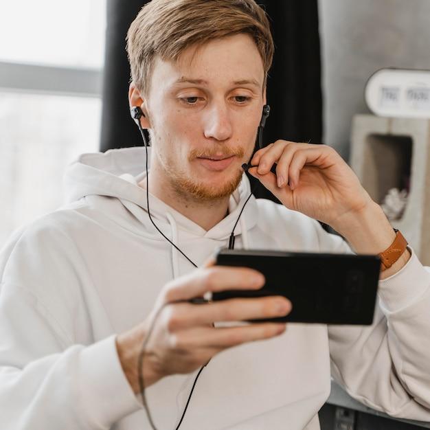 Мужчина среднего кадра с телефоном и наушниками Бесплатные Фотографии
