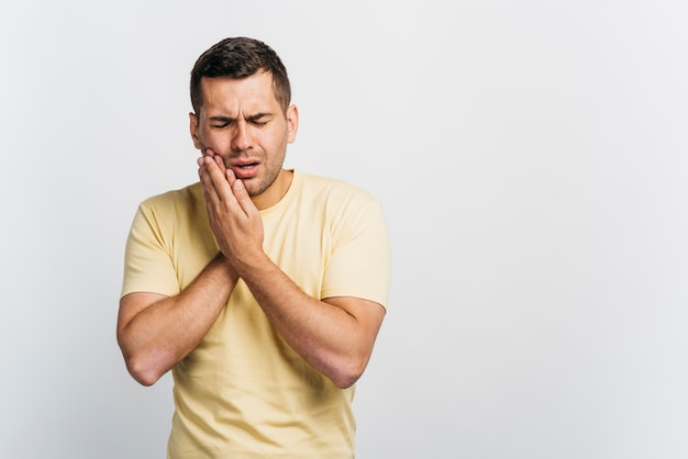 Medium shot man with tooth pain Premium Photo