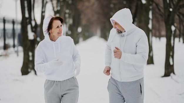 Uomo e donna di colpo medio che corrono Foto Gratuite