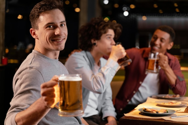 Uomini di tiro medio che bevono birra Foto Gratuite