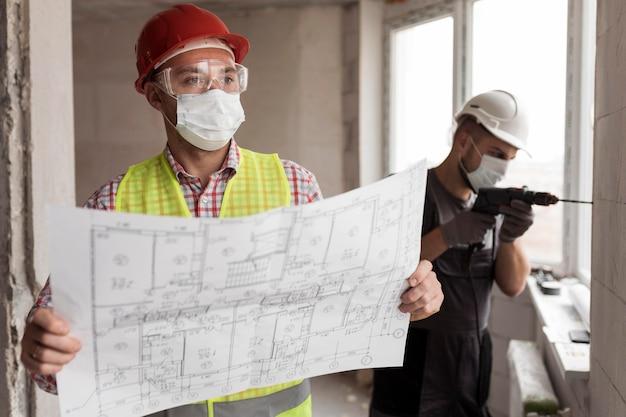 プロジェクトとドリルでミディアムショットの男性 無料写真