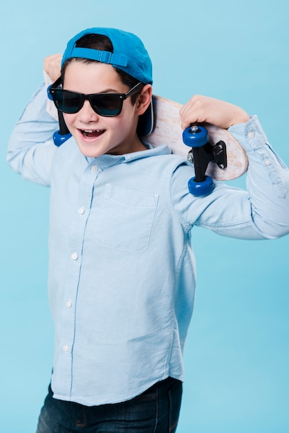 Medium shot of modern boy with skateboard and sunglasses Free Photo