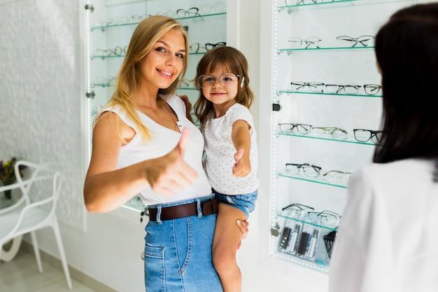 Medium shot of mom and daughter at optician shop Free Photo