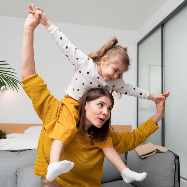 Средний план мать и девочка в помещении Бесплатные Фотографии