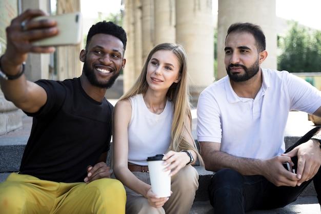 Medium shot multicultural friends taking selfies Free Photo