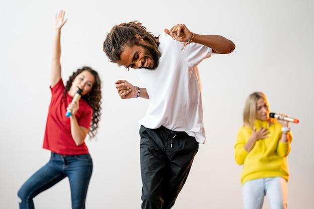 Средний выстрел многорасовых людей, поющих и танцующих Бесплатные Фотографии