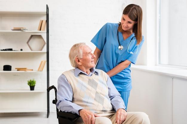 老人を見てミディアムショットの看護師 Premium写真