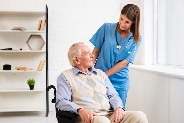 Medium shot nurse looking at old man Free Photo