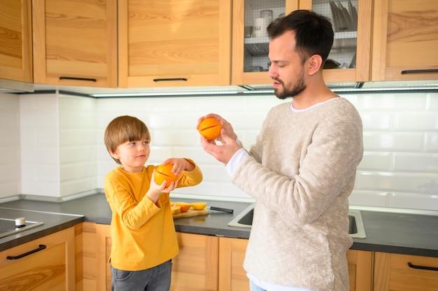 Средний снимок ребенка и отца на кухне Бесплатные Фотографии