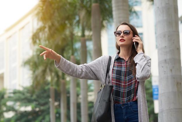 Средний снимок городского жителя, взявшего машину с жестом Бесплатные Фотографии