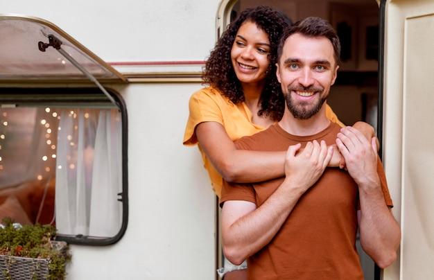 Средний снимок счастливой пары, стоящей перед автофургоном Бесплатные Фотографии