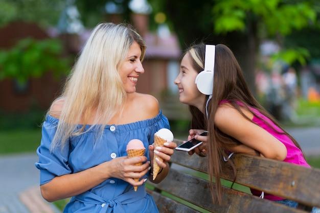 Средний снимок мамы и дочки с мороженым Бесплатные Фотографии