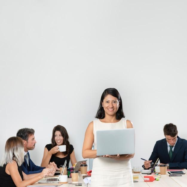 Средний снимок женщины, держащей ноутбук Бесплатные Фотографии