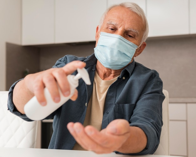 Medium shot old man pouring disinfectant Free Photo