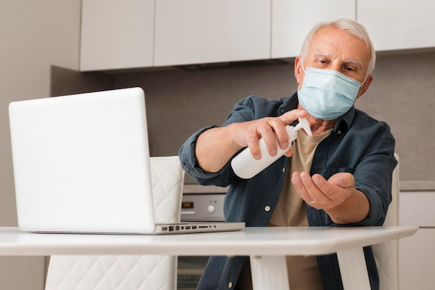 Medium shot old man using disinfectant Free Photo