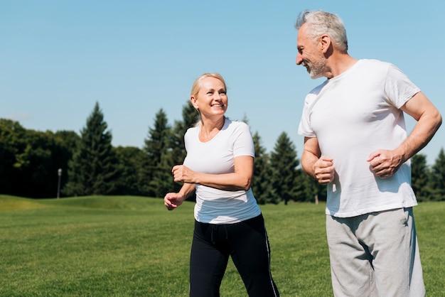 Medium shot old people running outdoors Free Photo