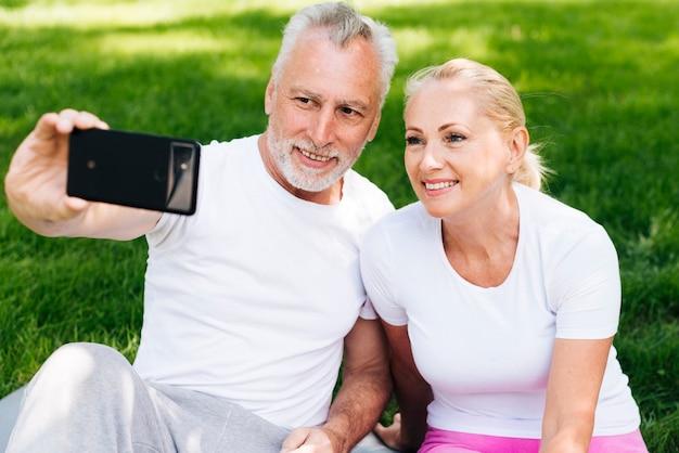 Medium shot old people taking selfies outdoors Free Photo