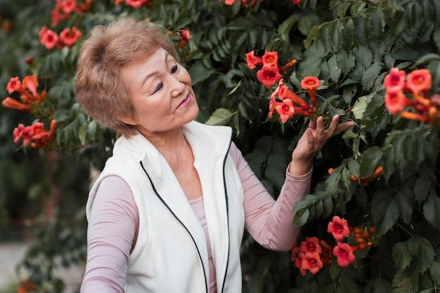 花でポーズをとるミディアムショット老婆 無料写真