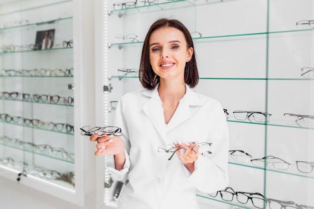 Medium shot of optician holding glasses frames Free Photo