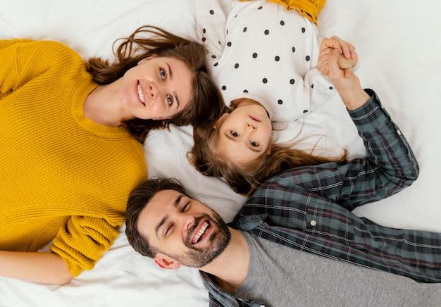 중간 샷 부모와 아이가 침대에 평평하게 누워 무료 사진