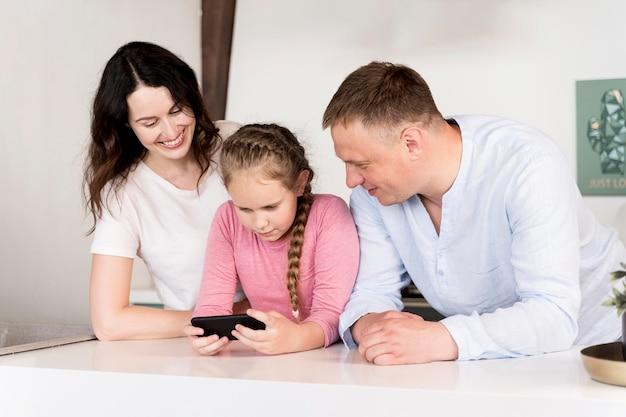 ミディアムショットの両親と子供と電話 無料写真